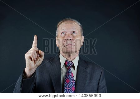 Business man looking up, finger up, senior man closeup portrait isolated on black background. Emotions, facial expression and people concept