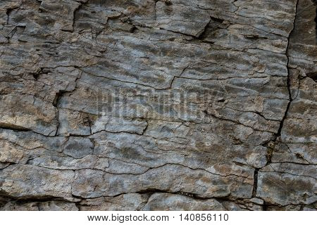 Stone wall of rock with cracks. .