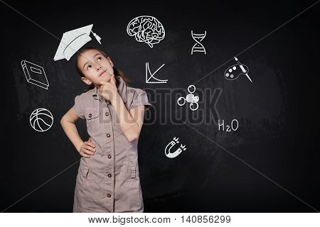 Small girl in imaginary graduation cap thinking. Thoughtful, pensive child consider something. Smart schoolgirl studio portrait near chalkboard with education icons. Studying science concept.
