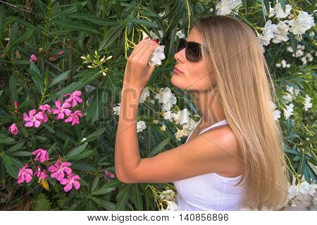 beatiful young woman smelling flower in garden