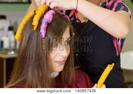 Young girl in hair dressing salon. Close up view. Hair curlers