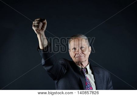 Happy Caucasian businessman on black background, one fist up, senior man closeup portrait isolated on black background. Emotions, facial expression and people concept