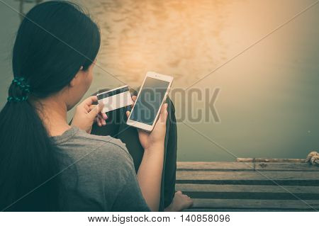 Weekend trendy lifestyle. Woman using phone for on line payment and another hand holding credit card while sitting outdoor in morning time. electronic business payment concept with vintage filter effect