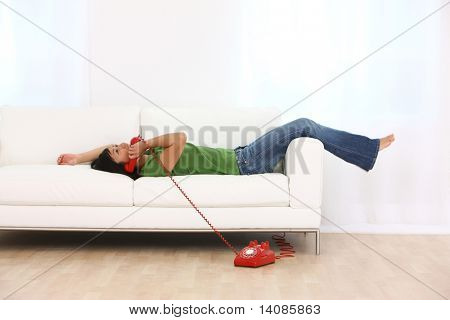 Young woman laying on couch talking on red retro telephone