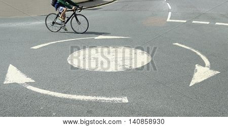 Small white roundabout with bicyclist passing by