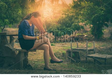 Abstract scene of young woman using her smartphone seriously while sitting outdoor on wood chair in morning time on weekend. Phone addiction concept with vintage filter effect