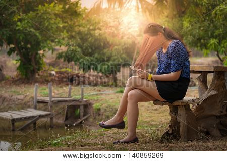 Abstract scene of young woman using her smartphone seriously while sitting outdoor on wood chair in morning time on weekend. Phone addiction concept.