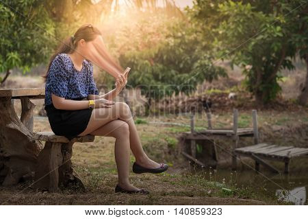 Young woman using her smartphone seriously while sitting outdoor on wood chair in morning time on weekend. Phone addiction concept.