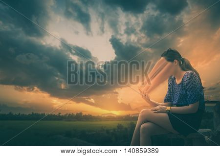 Abstract scene of young woman using her smartphone seriously while sitting outdoor on wood chair in morning time on weekend with blurry nature background. Phone addiction abstract concept with vintage filter effect
