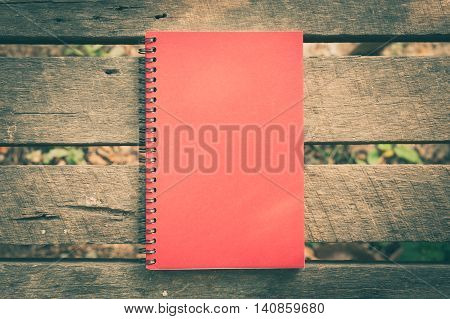 Red cover notebook with blank area on front cover on outdoor rustic wood table in morning time with vintage filter effect. Vintage notebook background concept