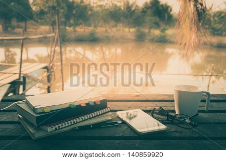 Smartphone notebooks coffee cup glasses and pen put down on outdoor wood table in morning time on weekend. Freelance business working concept with vintage filter effect