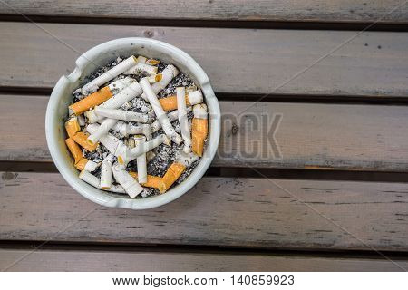 Various cigarette butts in dirty full ashtray