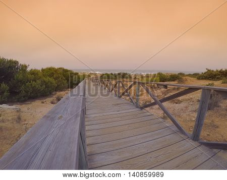 wooden path with railings leading to coast against of seascape at sunset.Copy space