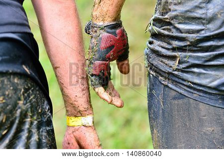 Close-up of unrecognizable people in mud while passing the extreme obstacle race