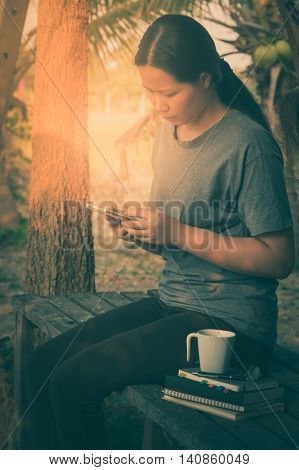 Young woman using her smartphone seriously while sitting in outdoor park on wood table in morning time on weekend. Freelance business working and phone addiction concept with vintage filter effect