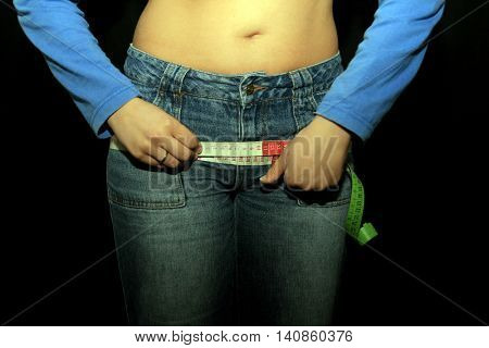 measuring tape around womans trousers, slim photo