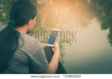 Weekend morning lifestyle. Young woman using her mobile phone seriously while sitting outdoor beside river in morning time. Freelance working and phone addiction concept with vintage filter effect