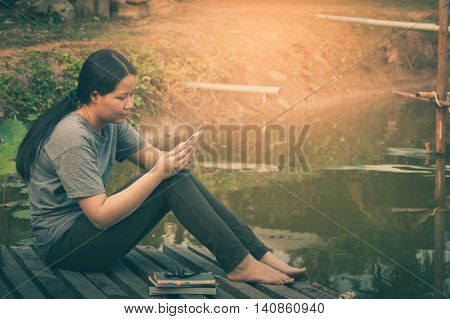 Weekend morning lifestyle. Young woman using her mobile phone seriously while sitting outdoor beside lake in morning time. Freelance working and phone addiction concept with vintage filter effect