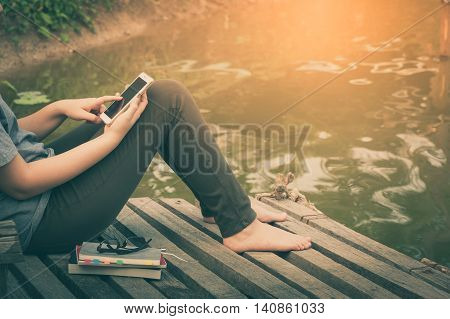 Weekend morning lifestyle. Woman touching on mobile phone screen while sitting outdoor with notebooks pen and glasses in morning time. Freelance working and phone addiction concept with vintage filter effect