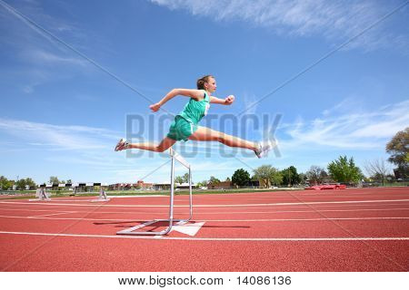 Woman jumping over hurdle