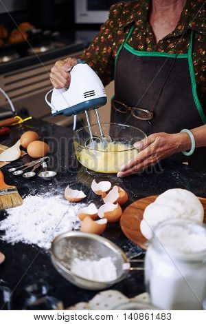 MAture woman whisking eggs with electric mixer