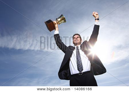 Businessman celebrating with trophy