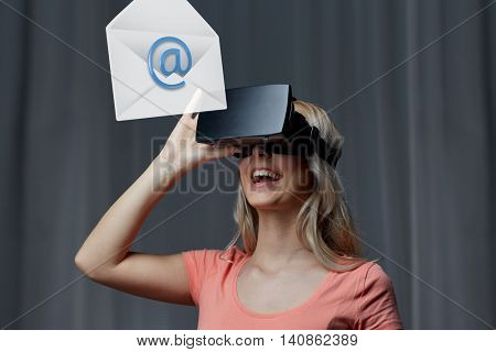 technology, virtual reality, cyberspace, entertainment and people concept - happy young woman with virtual reality headset or 3d glasses at home looking at email icon projection