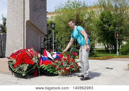 The Man Puts Flowers Before A Monument