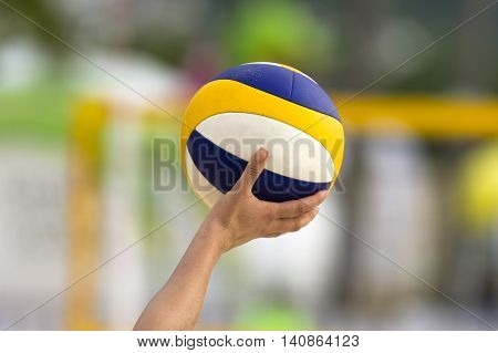 Volleyball is a volleyball being held up by a volleyball player ready to be served.
