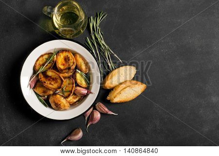 Baked potato with rosemary and garlic on the black background
