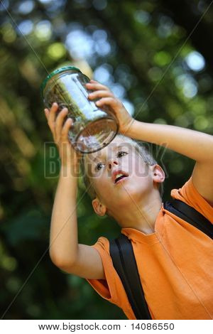 Young boy looking at bug in jar