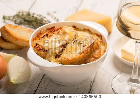 French onion soup with its ingredients on the white table (traditional cuisine)