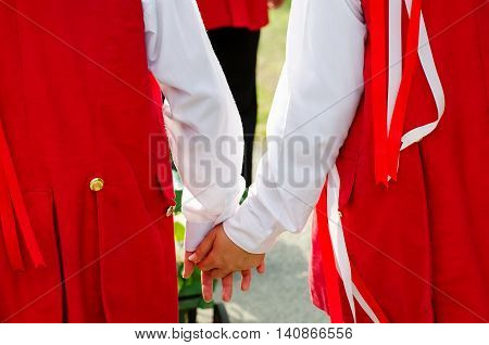 Young lovers in folk costume holding hands at moravian feast.