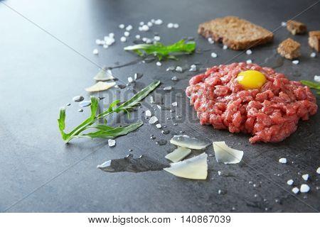 Tartare steak with ingredients on grey background