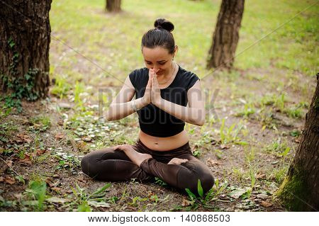 Portrait of smiling beautiful sporty young woman working out in park alley, standing with palms touching in Namaste gesture.
