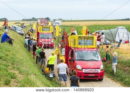 Quievy, France - July 07 2015: Cofidis Caravan during the passing of the Publicity Caravan on a cobblestoned road in the stage 4 of Le Tour de France on July 7 2015 in Quievy France. Cofidis in an important French money lending company.