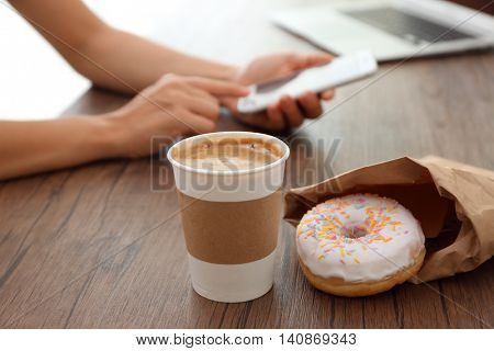 Paper cup of coffee and doughnut on wooden table closeup
