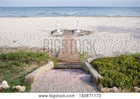 Wooden access footpath to the beach. Picture taken in Santa Pola town. It is a coastal town located in the comarca of Baix Vinalopo in the Valencian Community Alicante Spain by the Mediterranean Sea.