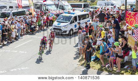 Col du Glandon France - July 23 2015: Nelson Oliveira of Lampre-Merida Team and Danilo Wyss of Team Sky riding in a beautiful curve at Col du Glandon in Alps during the stage 18 of Le Tour de France 2015.