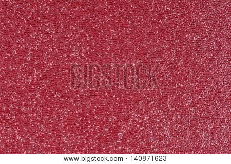 Red embossed decorative leatherette texture background, close up