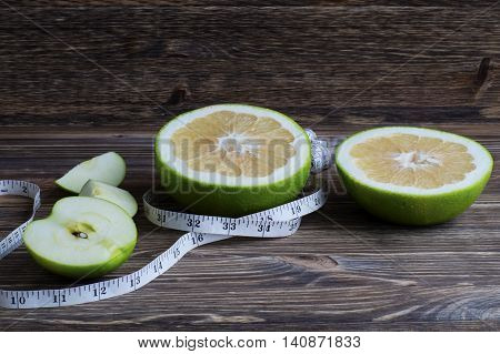 Dieting concept. Closeup Pamela fruit and apples with measuring tape on table