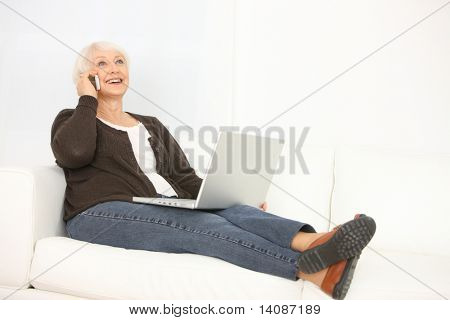 Senior woman with laptop talking on cell phone