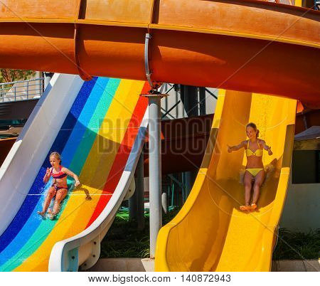 Two children on water slide at water park thumb up. Outdoor park.