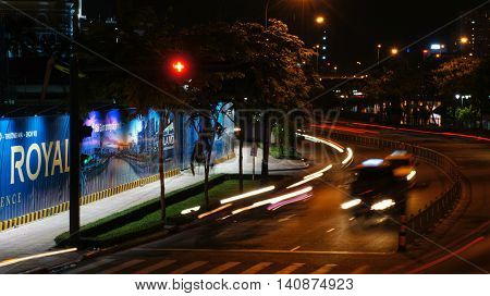 Ho-Chi-Minh-City (former Saigon), Vietnam, 22nd July 2016. Night scene of lights of unfocused blurry cars and motorcycles in motion approaching an intersection with a red traffic light.
