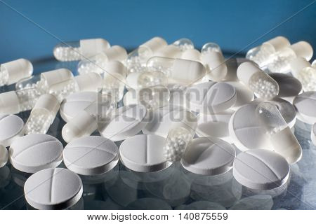 Medicine pills and capsules with blue background