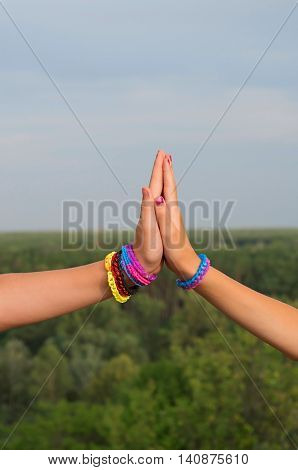 children's hands with colored bracelets touch palms