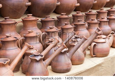 many clay retro pots with long spouts