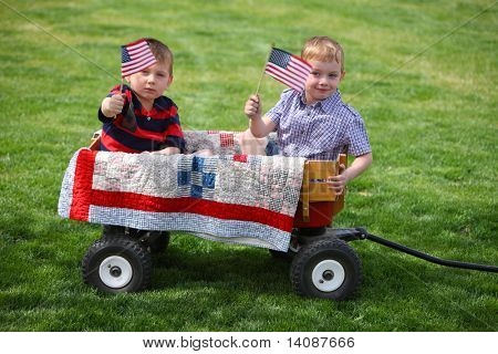 Two young boys sitting in wagon with American Flags