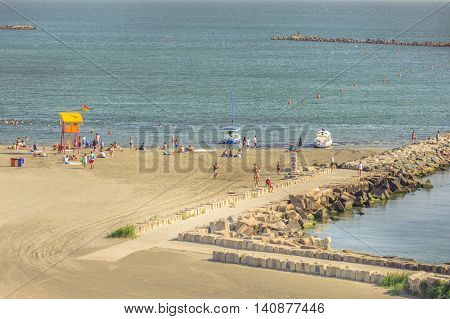 Mamaia Romania - July 18 2016: People resting on beach on in Mamaia Romania. Mamaia is the largest and best known resort on Romanian Riviera. It's situated on 8km long and 300m wide sandy land strip at the Black Sea.