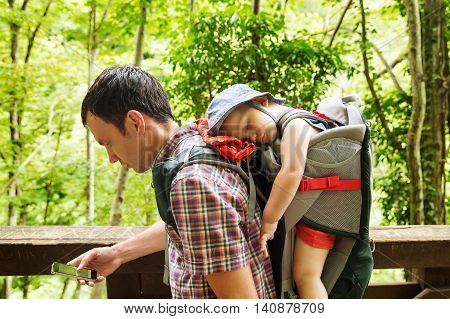 Active Family Hiking With 1,5 Years Child In Carrier On The Background Of A Nature.